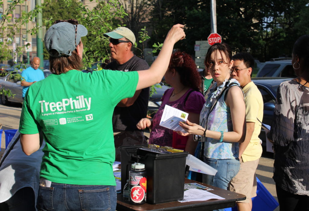 Staff person is green TreePhilly shirt points to trees for residents